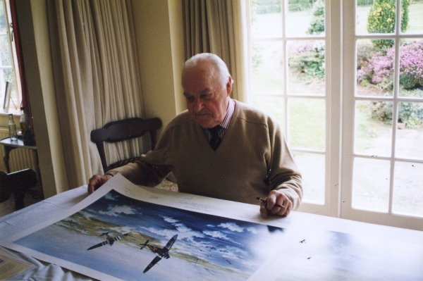 Signing the print <i>Combat Over Normandy</i> by Graeme Lothian.